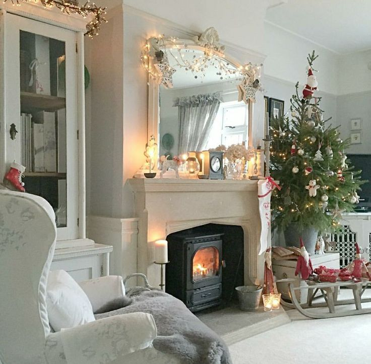 English living room at Christmas, woodstove inset into hearth, large arched overmantel mirror above.