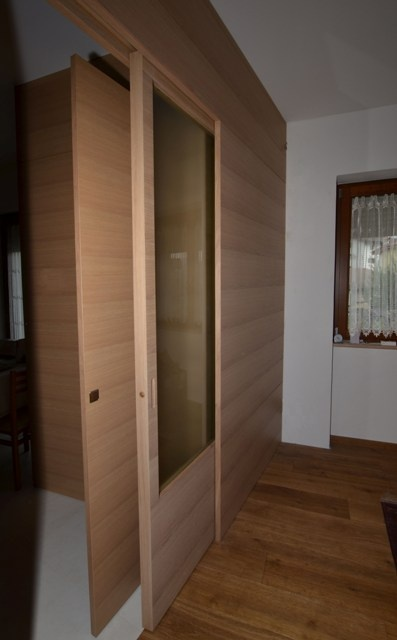 Sliding door, matching with wall made of streaked durmast. Satin glass door.