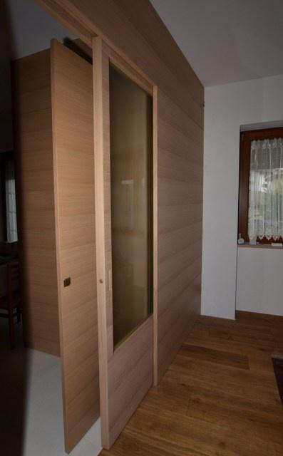 Sliding door, matching with wall made of streaked durmast. Satin glass door.