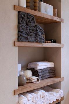 étagère brute créée uniquement par des planches de bois insérées dans le placo pour ranger les serviettes rouges