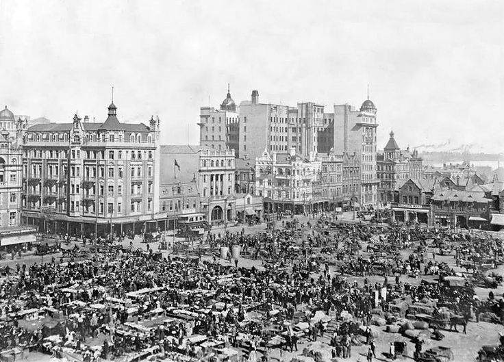 This view depicts a busy scene. On sale days, part of the Square is devoted to the selling of all kinds of merchandise by public auction. In the background, the headgears of some of the mines can be seen.   Market Square was a long, rectangular area, extending from Rissik Street to Sauer Street and bounded by President and Market Streets.