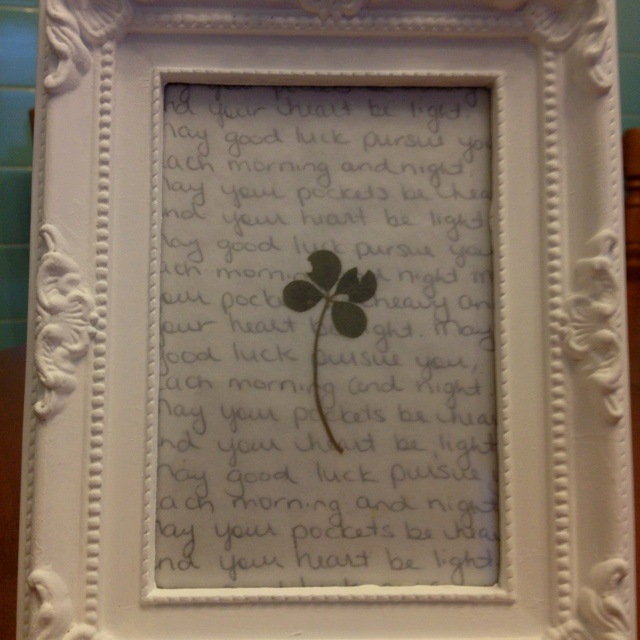 "Pressed Four leaf clover, white hand painted frame with handwritten verse in background ""May your pockets be heavy, and your heart be light. May good luck pursue you, each morning and night."""