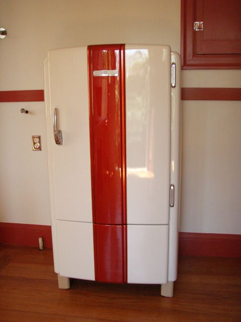 "1940s General Electric refrigerator, customized in 2009 ""The base color is an off white with an orange pearl over the top.  The center section has been flaked out and covered with a tangerine candy to match the trim color I used in my kitchen.  Black and tan pinstriping was used to help define the raised center sections on the door and lower panel."""
