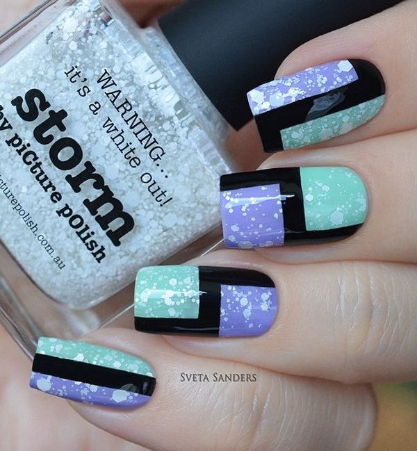 A refreshing green and purple abstract nail art design. This design is perfect for spring because of its light colors and the water splatter details on top. The black bold lines separating the colors help bring life to the design.