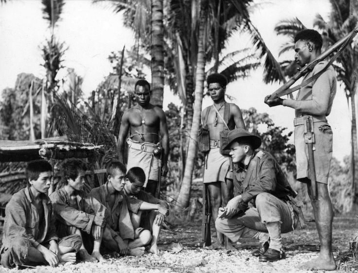 Japanese soldiers taken as prisoners by Australian forces at Ulebilum Ridge during the New Guinea Campaign are interrogated by an Australian soldier as three armed Papuan scouts stand guard (July 1945).