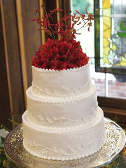 Brides: Wedding Cake with Red Flower Topper. Agnes Mitchell of Three to Go Bake Shop made this buttercream-frosted cake. A lily of the valley design circled the base of each tier. Judy Wallace of Simply Elegant Weddings topped off the cake with alstroemeria and Italian ruscus to add color to the dessert.