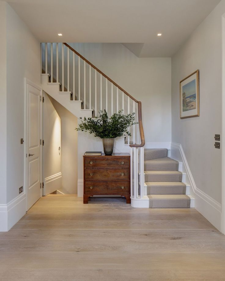 Plain spindles on the bannister. white painted stairs. Wooden handrail. Grey runner. Its the curve that makes it.