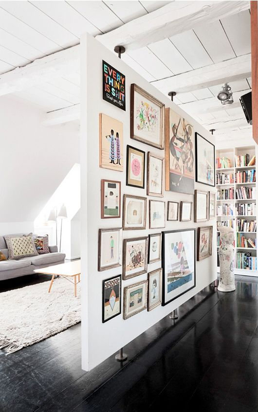 """If you have a large room, consider constructing a divider wall. Leave a little space at top and bottom for airflow and visual space. Use o e side as a media center and the other as an """"art gallery"""" in your home. - Rebecca Rebouche"""