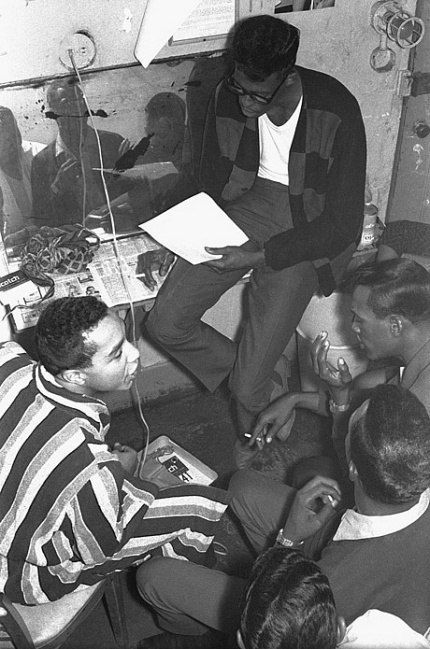 "Backstage at the Apollo Theater, 1964, the Temptations practice the lyrics to their soon-to-be-a-hit song ""My Girl,"" coached by Smokey Robinson (who wrote the song with fellow Miracles member Ronald White). Clockwise from top: David Ruffin, Eddie Kendricks, Paul Williams, Otis Williams, and Smokey Robinson. © Michael Ochs Archives."