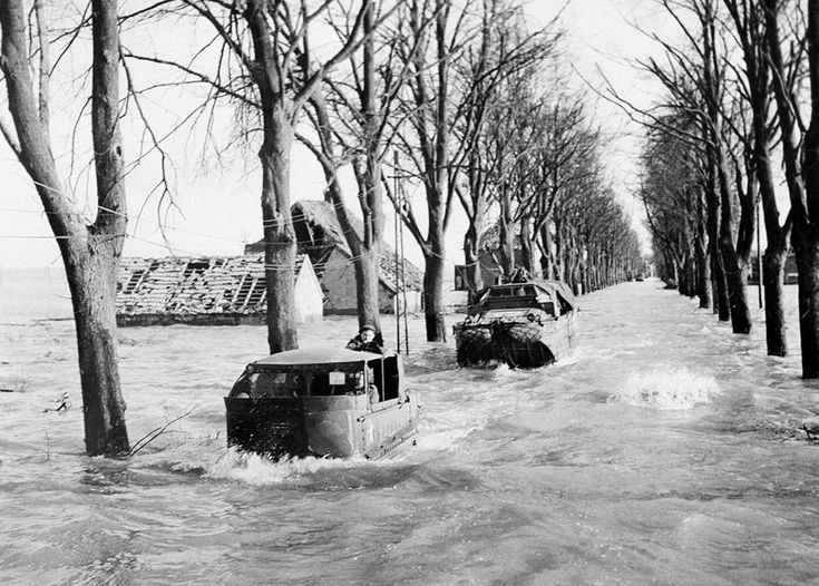 A party sets out to repair telephone lines on the main road in Kranenburg on February 22, 1945, amid four-foot deep floods caused by the bursting of Dikes by the retreating Germans. During the floods, British troops further into Germany have had their supplies brought by amphibious vehicles