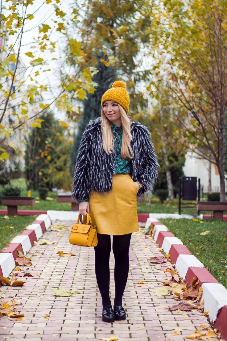 Autumn, winter look with yellow a line skirt, yellow bag from Guess, black faux fur jacket, green shirt, black tights, black loafers. ootd, outfit, street style By Andreea Ristea