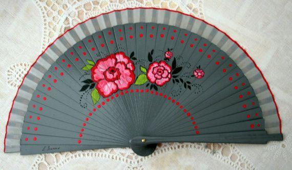 Abanico español pintado a mano. Flores y lunares rojos sobre fondo gris. Gris y rojo.