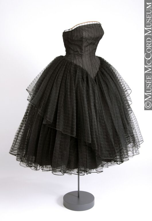1956.  Beautiful example of a party dress, though it borders on the costume due to the deepness of the front shaping on the bodice.  I like the striped sheer overlays, and would add a bolero or portrait collar drape from same.