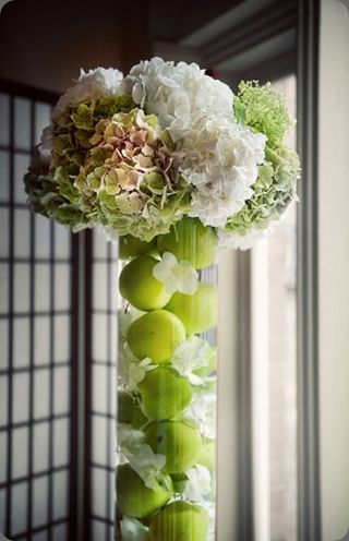 Green and white hydrangea #centerpiece in cylinder of floating green apples - Verbena Floral Design