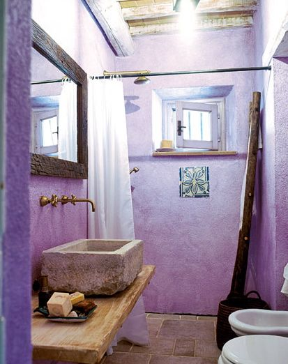 Tiny rustic Italian cottage bathroom features stone sink, white toilet bowl, white tub, a shower room & wooden rustic mirror