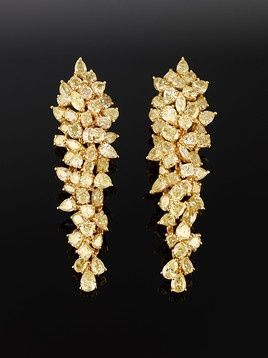 A beautiful pair of earrings composed of  cascades of natural fancy yellow diamonds ~ M.S. Rau Antiques