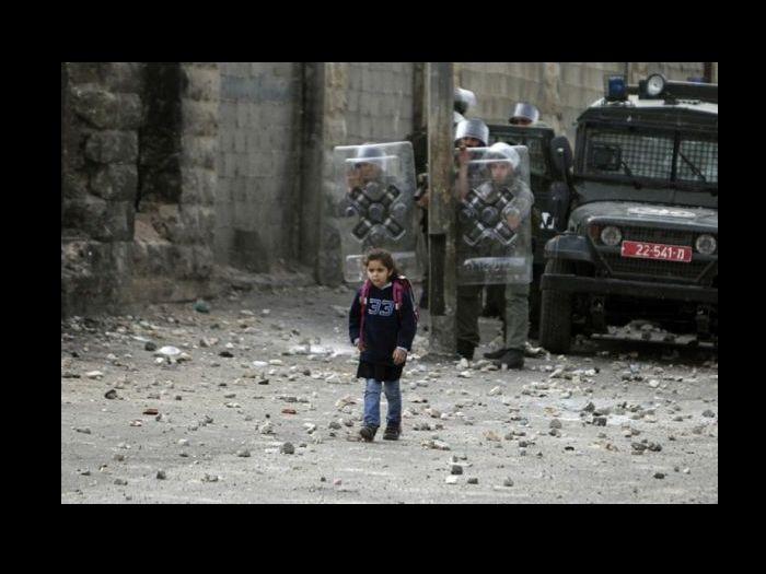 O fotógrafo Ammar Awad da Reuter tirou esta foto em 2010. Diferente das outros crianças, esta menina não precisa atravessar rios ou montanhas, mas um confronto armado entre israelenses e palestinos no campo de refugiados de Shuafat, perto de Jerusalém. Na rua, podem-se ver pedras que foram atiradas por manifestantes em direção a tropa israelense que usa escudos de proteção.