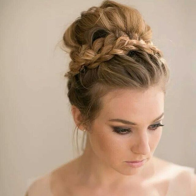 "We love the trend away fom rigidly lacquered up dos to softer ""undone"" bridal hair like this braided bun. #braids #plait #bridalhair #wedding"