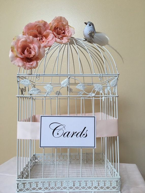 The perfect complement to any love birds themed wedding. You do not have to purchase with little bird. This decorative birdcage is customizable and designed from metal wire and painted with a stylish white finish. White and Black birdcage is available, but requires a 3 week processing time. This birdcage is customizable with your choice of ribbon color, flower, embellishments & card sign. This is a large cage and will hold approximately 150+ cards (wedding of 300 people) Thank you