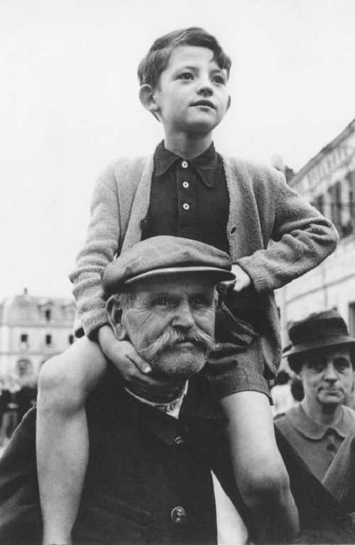 """""""A boy and his grandfather listen to General De Gaulle's speech after the liberation of the city ~ Chartres, France -          August 23, 1944) • photo: Robert Capa"""