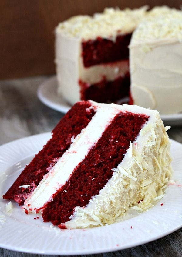 Red Velvet Cheesecake Cake recipe:  two layers of red velvet cake with a layer of cheesecake sandwiched in the middle.  All covered by a thick layer of rich cream cheese frosting and white chocolate shavings.  Great Easter dessert recipe, Mother's Day dessert recipe or birthday cake recipe.  Everyone always raves about this cake and thinks that you ordered it from a bakery!
