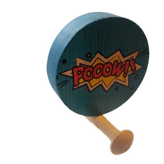 Circular wooden wall hook. Comic strip words POOOW.