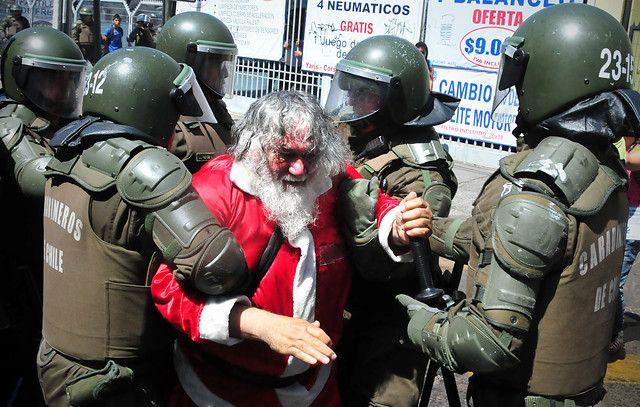 22 de Diciembre de 2011/SANTIAGO Un hombre disfrazado de Viejo Pascuero, es detenido por carabineros, luego que el primero intentara detener un carro lanzaaguas durante la marcha no autorizada de estudiantes. FOTO:SONIA ROSSEL/AGENCIAUNO