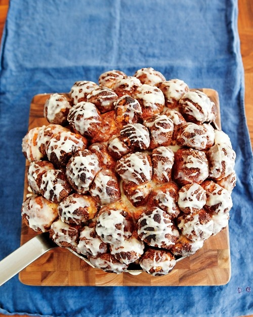 Cinnamon-Bun Bites - Bite-size rounds of buttery dough are dipped in cinnamon sugar and piled into a baking dish to create this irresistible breakfast bread.