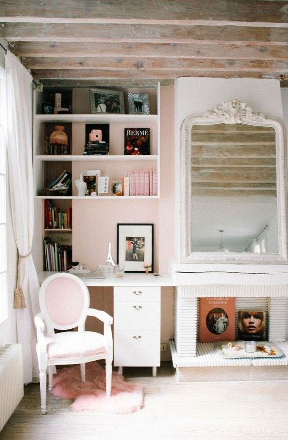 Pastel pink walls in this built-in office space with white shelving and desk space, a pink fur rug and armchair, all set next to a large white mirror and mantel.
