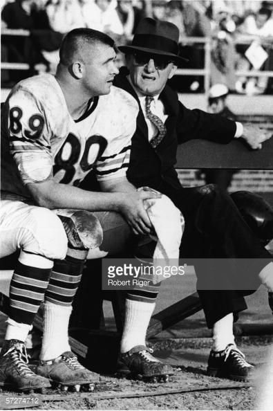 American football coach owner and former professional football player George Halas head coach for the Chicago Bears sits on the bench with his legs...