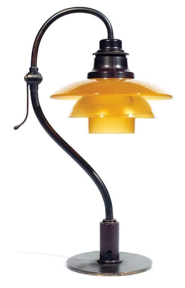 """Tajan - Poul HENNINGSEN (1894-1967) & LOUIS POULSEN (Éditeur) Lampe de bureau """"PH 2/2"""", base circulaire en laiton patiné d'où s'élève un fût courbe en laiton patiné muni d'une bague inférieure en bakélite brune à interrupteur traversant, bras coudé supérieur orientable par une virole à mi-hauteur munie d'une prise, structure en bakélite brune maintenant les déflecteurs en verre teinté miel à intérieur satiné, structure d'accroche en aluminium, coupelle interne formant dôme en verre satiné."""