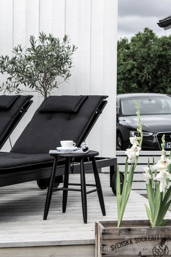 Outdoors, beautiful wood veranda with olive trees and black furniture, stool, chair
