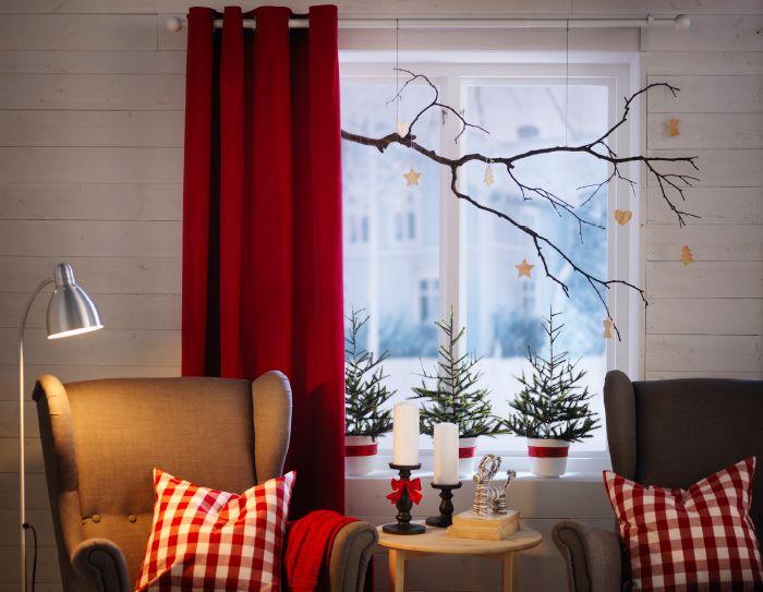 Zwei Ohrensessel, die vor einem Fenster stehen, auf dessen Fensterbank geschmückte künstliche FEJKA Weihnachtsbäume stehen.