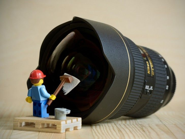 Lego minifigure of man cleaning the lens of a DLSR camera