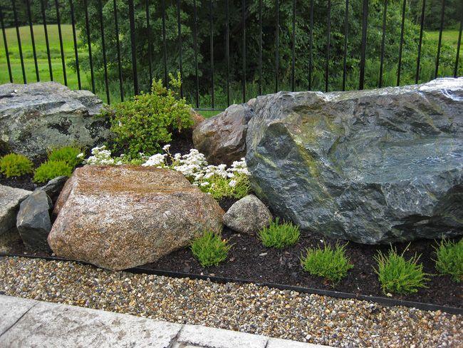 Attractive Rock Garden Ideas Beside Black Fence