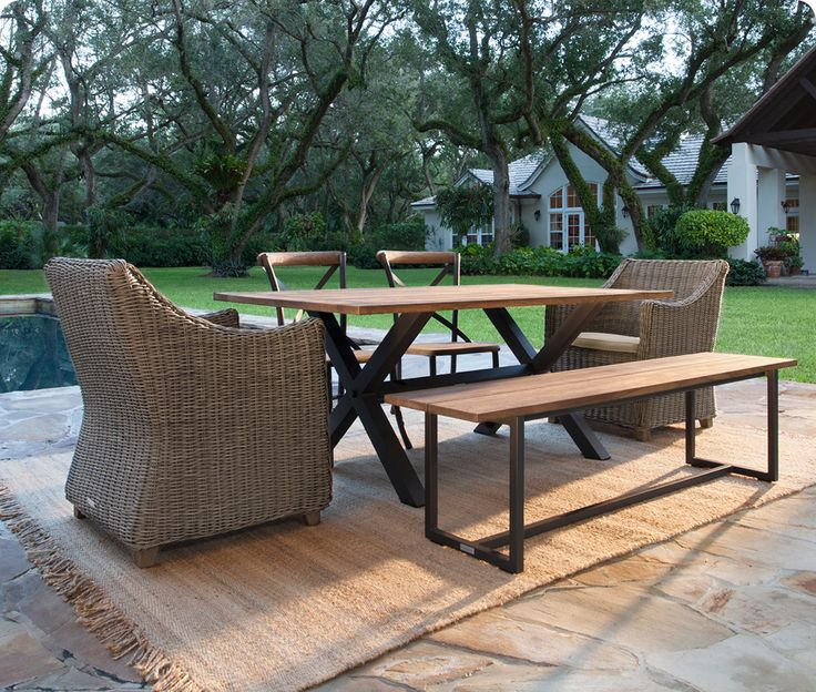 Mix up your outdoor seating by pairing a wood bench and dining chairs with wicker armchairs.