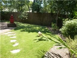 919B Fisher houston, TX 77018: Photo Tropical and lush backyard with large brick paver patio perfect for grilling and dining.  Enjoy serene views and sounds from Asian inspired ornamental fountain.  Professionally landscaped with sprinklers.