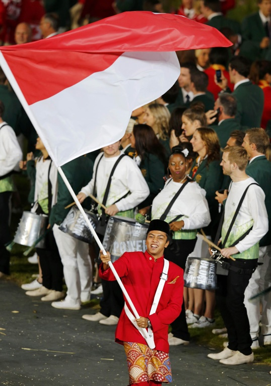 Indonesia's flag bearer, Gede Sudartawa, holds the national flag as he leads the contingent in the athletes' parade during the opening ceremony of the 2012 summer Olympic games. (Agency Photo).