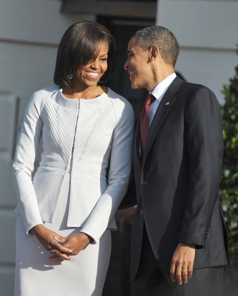 whispering something to his first lady while awaiting the British Prime Minister.....he's just the coolest and so down-to-earth