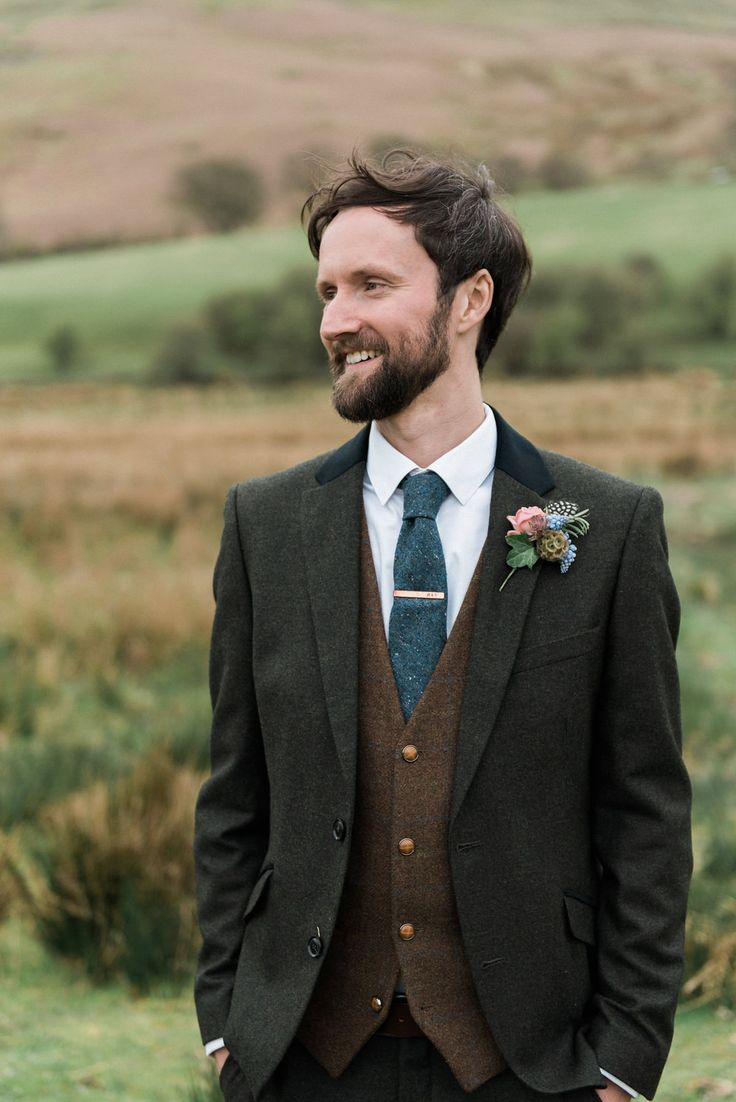 Groom wears a grey tweed suit with brown tweed waist coat and blue tweed tie. Photography by http://www.folegaphotography.co.uk/