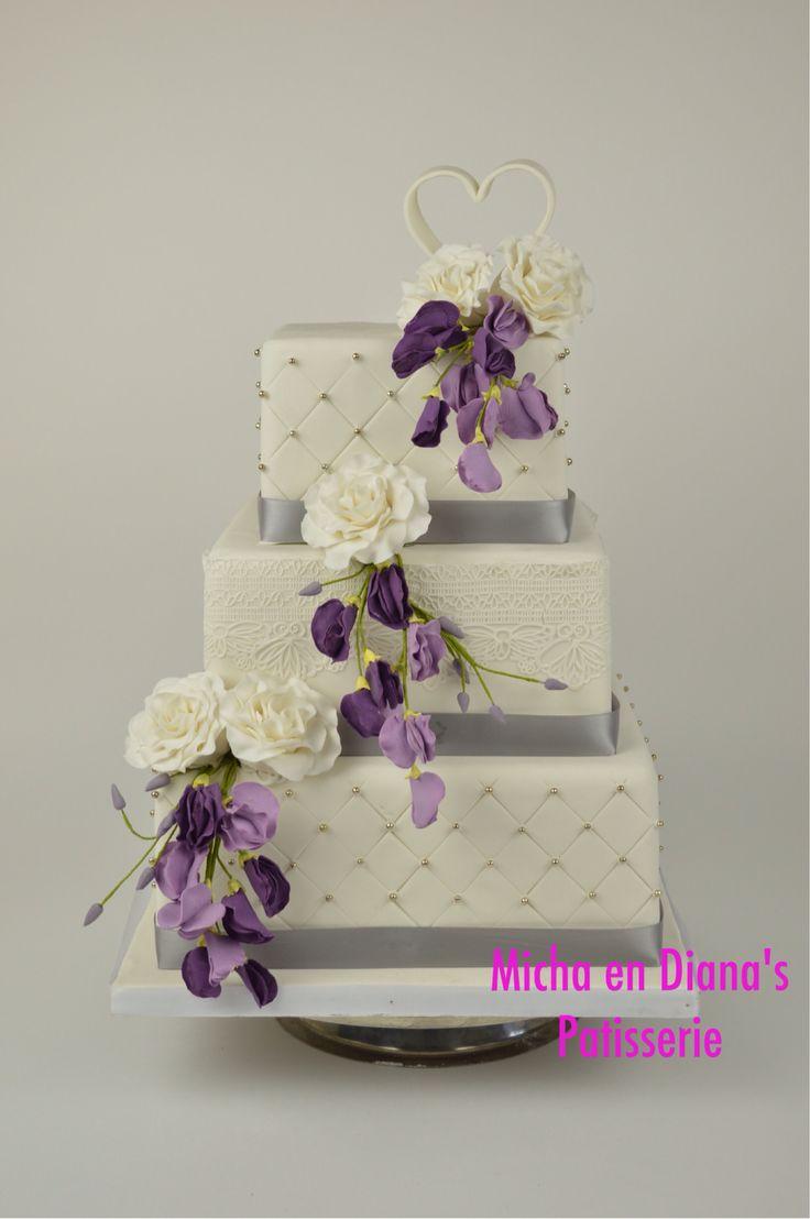 Vierkante bruidstaart met bloemen op ijzerdraad.