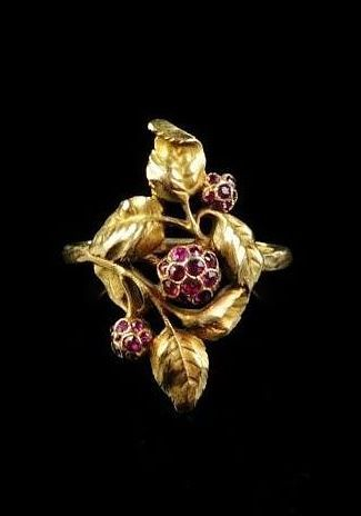 An 18k gold Art Nouveau ring designed as entwined leafs highlighted with three ruby set flowerheads. Makers mark of Julien Duval www.dekkerantiquairs.nl