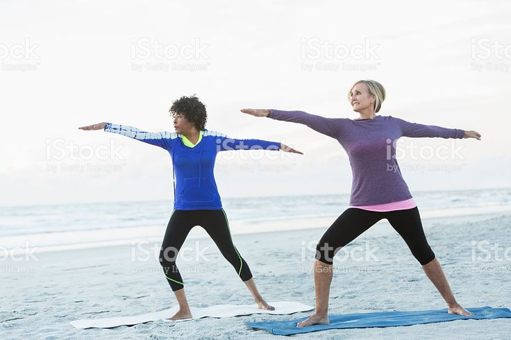 Two mature women exercising on beach royalty-free stock photo