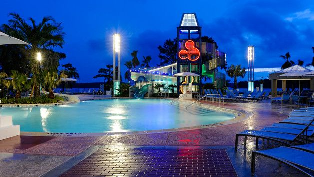 Nighttime view of a corner of Bay Cove pool, poolside lounge chairs, and a 20-foot high waterslide