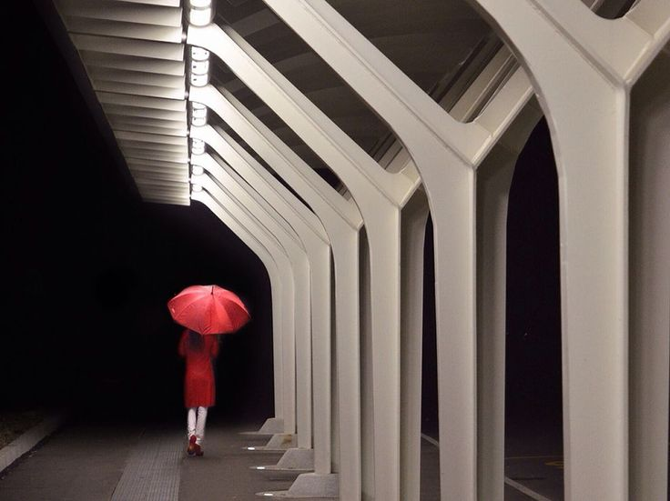 Picture of a woman walking with a red umbrella at a train station in Italy