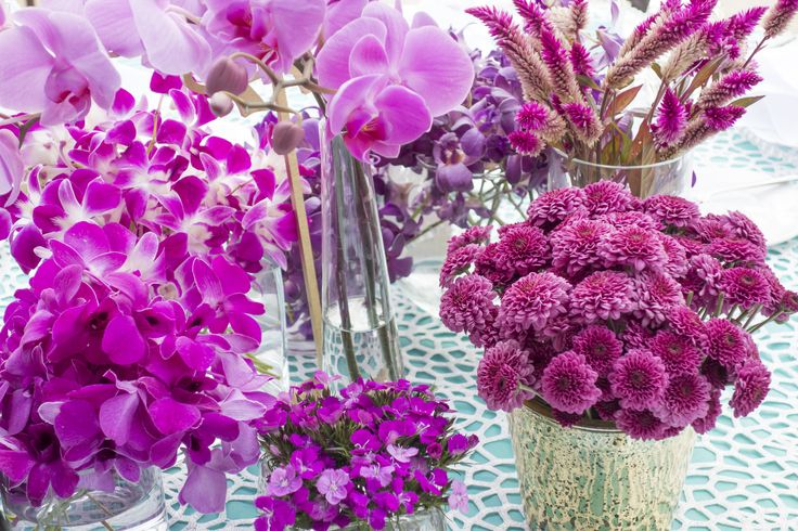 Elegant centerpieces with bright purple blooming orchids, little carnations in assorted decorative vases