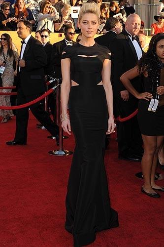 Amber Heard, lleva un vestido negro de corte 'sirena' con varias aberturas en el cuerpo, de Zac Posen (colección 'Pre'-Fall 2012) y joyas de H. Stern.