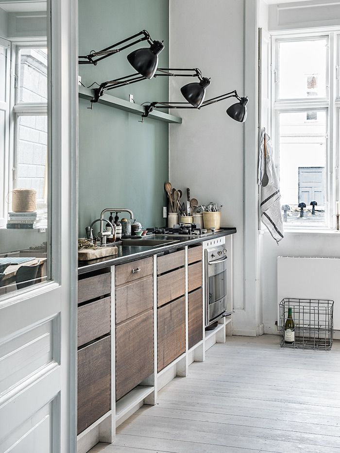 Kitchen: sage green feature wall splashback, black lamps, matt wooden cabinets, black benchtop, pale limewashed timber floorboards, white walls