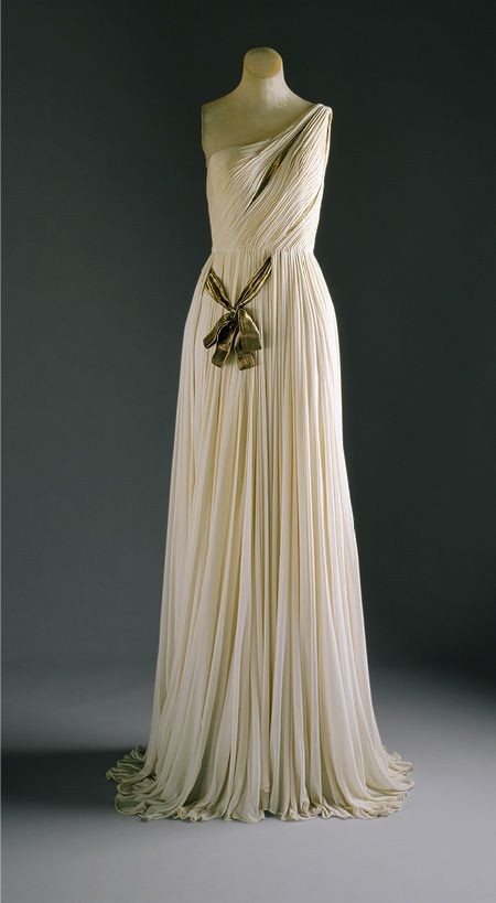 Grès was able to create pieces of increasingly complex drapery and pleating by tacking her difficult medium onto the rigid form of the shaping underbodice. Her lacing of a #gold lamé ribbon, which articulates the separate, vertically draped panels that run unbroken from neckline to hem, alludes to the girdling and quiver straps seen in classical renderings of #Artemis.