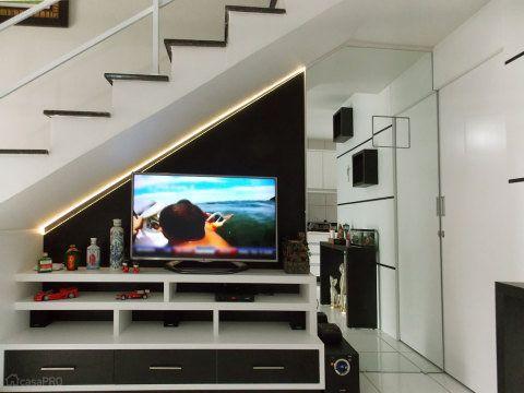 Coloque a TV na parede. Este espaço debaixo da escada abriga o móvel da TV com fita de led. Um painel com espelho esconde a caixa de luz. A porta de correr embutida para o lavabo recebeu um aparador e nichos na frente. Projeto de Adriana Angioleti, do CasaPro.